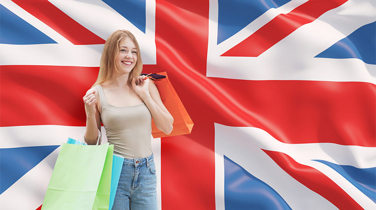 A happy young woman with the colourful shopping bags from the fancy shops. Great Britain flag background.